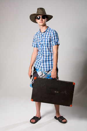 Portrait of a young tourist in a full-length looking away. A man wearing sunglasses and a hat holding a suitcase photo