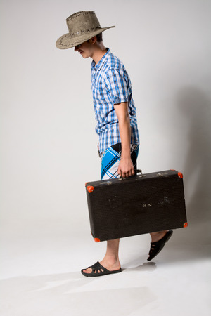 Portrait of a young man in a full-length coming from the suitcase. On a light background in the studio photo