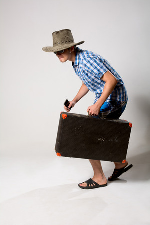 Portrait of a young man in a full-length coming from the suitcase. On a light background in the studio with a phone in his hand photo