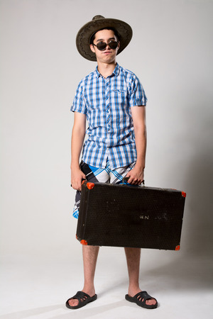 Portrait of a young tourist in a full-length looking away. Tired man with a suitcase with sunglasses and hat photo