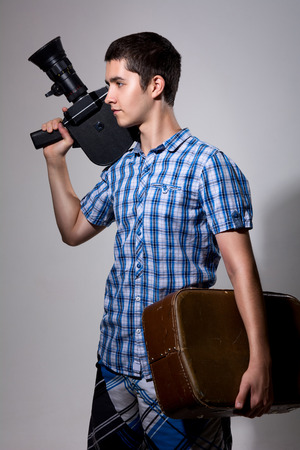 filmmaker: Young man filmmaker with old movie camera and a suitcase in his hand. Stock Photo