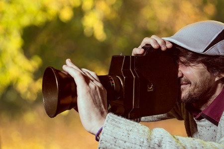 reportage: A man wearing a cap with an old movie camera. Shooting reportage in autumn