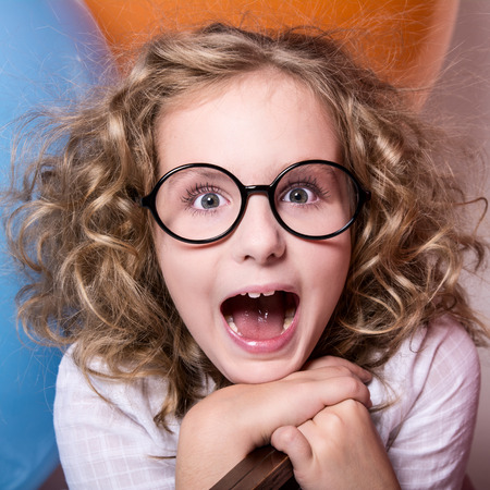 Happy surprised girl in glasses with an open mouth on a background of large balloons. square photo Stock Photo