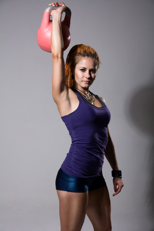 Portrait of young attractive female doing kettle bell exercise on grey background. Fitness woman working out. Crossfit exercise. photo