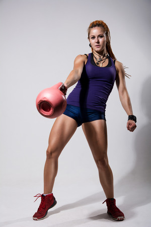 Portrait in a full-length of young attractive female doing kettle bell exercise on grey background. Fitness woman working out. Crossfit exercise. photo