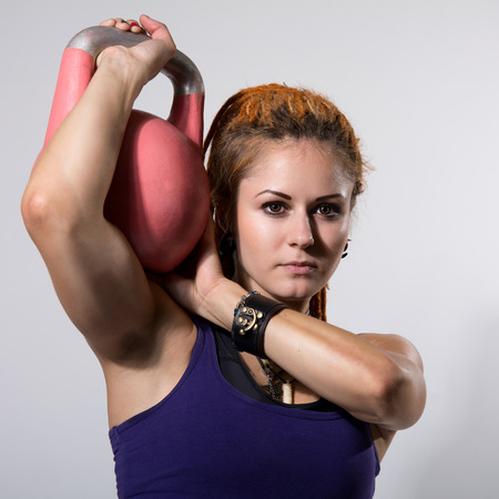 Portrait close up of young attractive female doing kettle bell exercise on grey background. Fitness woman working out. Crossfit exercise. square photo photo