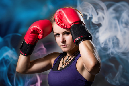 Portrait of beautiful girl with red boxing gloves. Фото со стока