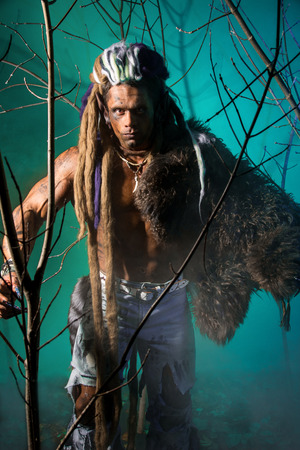 Portrait of a man walking a werewolf with a skin on the shoulder and with dreadlocks photo