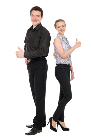 Side view portrait of happy couple showing thumbs up sign while standing back to back over white background. Vertical shot. photo