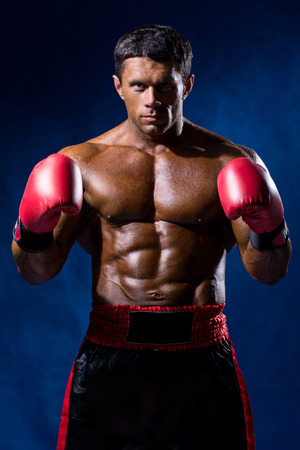 Boxer Boxing staring showing strength. Young man looking aggressive with boxing gloves. Caucasian male model isolated on dark background.