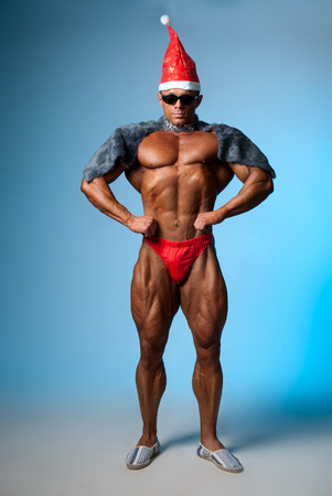 nipple man: Strong athletic man in a santa hat and dark glasses. Bodybuilder on a blue background. Christmas fancy dress Stock Photo