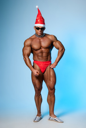 attractive man: Strong athletic man in a santa hat and dark glasses. Bodybuilder on a blue background. Christmas fancy dress Stock Photo