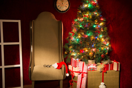 dacorated: Christmas decor with fir tree and an armchair. Gifts at the Christmas tree. Horizontal image. Stock Photo