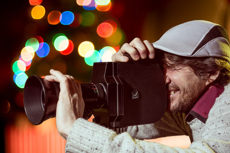 A man wearing a cap with an old movie camera. Shooting reportage, cinema, рождество Stock Photo