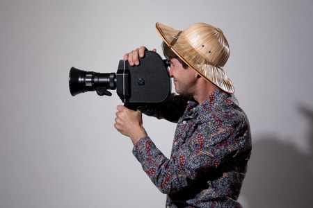 filmmaker: A man in a straw hat with an old movie camera on a gray background. Videographer to shoot reportage Stock Photo