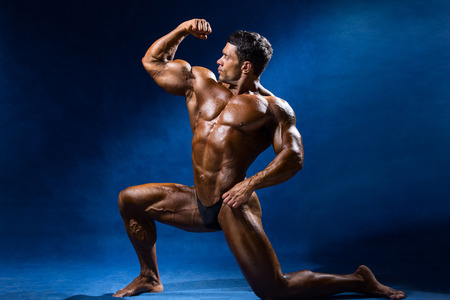 Strong muscular man bodybuilder shows his muscles. Sportsman fitness on a blue background