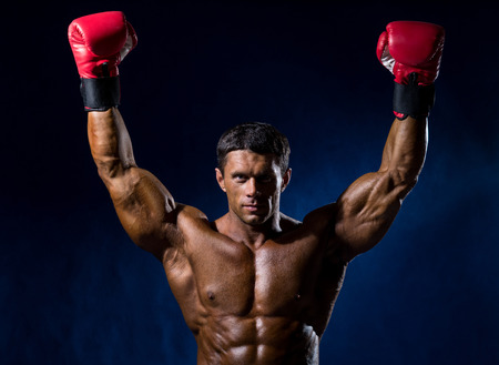 caucasians: Strong muscular boxer in red boxing gloves raised his hands above his head. Victory in a boxing match