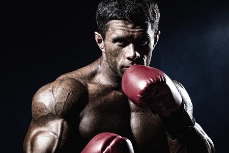 boxeador: Boxeador musculoso fuerte en los guantes de boxeo rojos. Un hombre en una postura de boxeo.