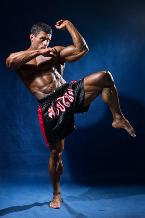 forearms: Thai boxer in full growth in a rack on a blue background. Stock Photo
