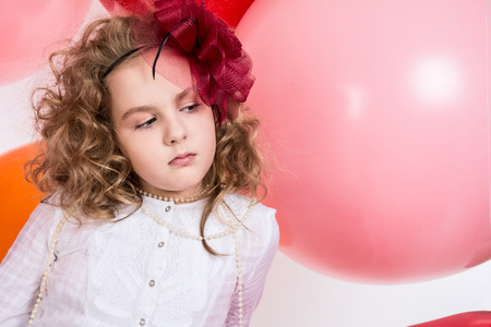 Portrait of teen girl in a hat and white dress on a background of big colored rubber air balls. Girl looking to the side photo