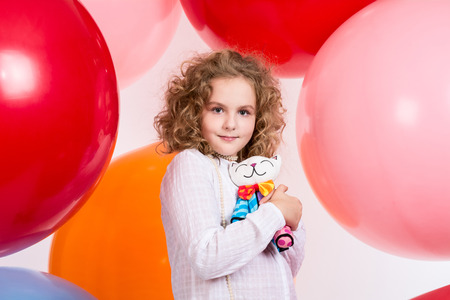 soft toy: Beautiful teen girl with a soft toy in hand over large rubber balloons.