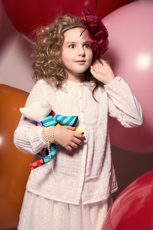 soft toy: Surprised girl in a red hat in a white dress with a soft toy in his hand looking to the side. Against the background of large rubber balloons. toned image Stock Photo