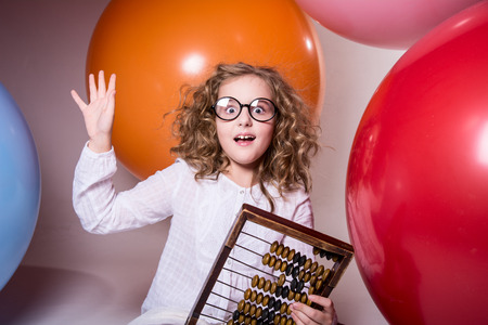 scores: Thoughtful curly teen girl in glasses with wooden abacus on the background of large rubber balls. Stock Photo