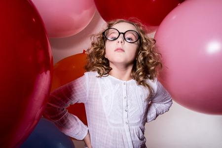 fantasque: Portrait de graves adolescente sur le fond de grandes balles en caoutchouc. Important, fille capricieuse