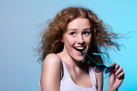 sexual position: Pretty young emotional girl in sunglasses looks toward the top on a blue  Stock Photo