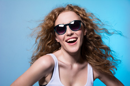 sexual position: Pretty young emotional girl in sunglasses on a blue