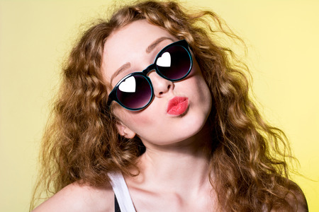 sexy girl posing: Pretty young beautiful girl in sunglasses makes lips kiss on the yellow background. Reflected in sunglasses with heart-shaped