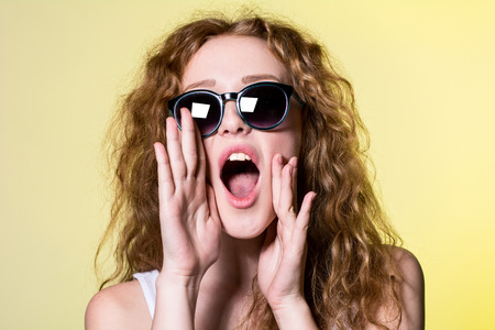 Nice girl with curly hair screaming. woman calls Stock Photo