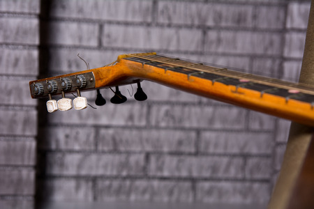 grief: Grief acoustic guitar on the brick wall background. Stock Photo