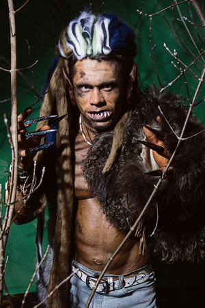 unas largas: Hombre lobo con las u�as largas y los dientes torcidos entre las ramas del �rbol.