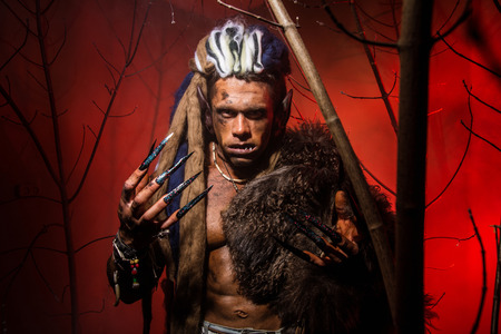 unas largas: Hombre lobo con las u�as largas y los dientes torcidos entre las ramas del �rbol. Sobre un fondo rojo con ramas