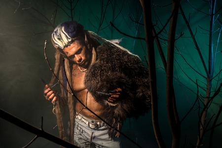 long nails: Werewolf with a skin on his skin and long nails among tree branches.