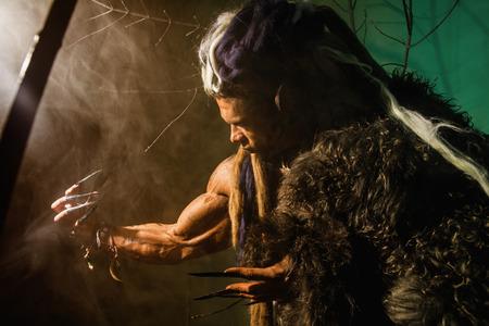 dark elf: Muscular man with skin and dreadlocks. Werewolf in the woods