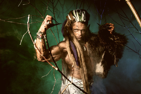 Muscular man with dreadlocks and skin through the trees and mist. photo