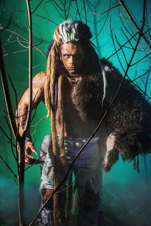 Muscular man werewolf goes through the woods. photo