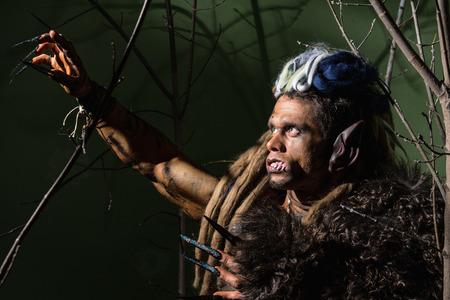 wilkołak: Wilkołak z długimi paznokciami i krzywe zęby wśród gałęzi drzewa.