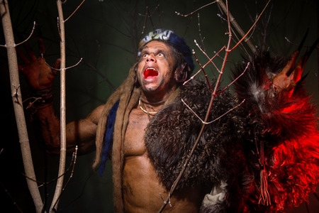 Muscular werewolf hair dreadlocks among the branches of the tree screaming. photo