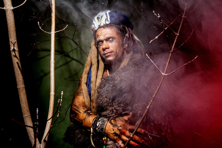 long nails: Werewolf with long nails and hair dreadlocks among the branches of the tree. Stock Photo