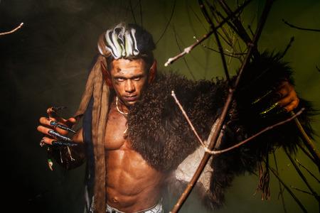 unas largas: Hombre lobo con una piel de su hombro y las u�as largas entre ramas de �rboles.