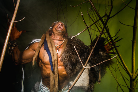long nails: Vicious werewolf with a skin on his shoulder and long nails among tree branches. Stock Photo