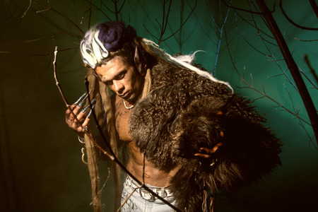 Muscular man with skin and dreadlocks among the trees. photo