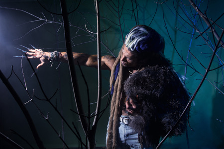 dark elf: Muscular man with dreadlocks and skin through the trees. Werewolf in the woods. Stock Photo
