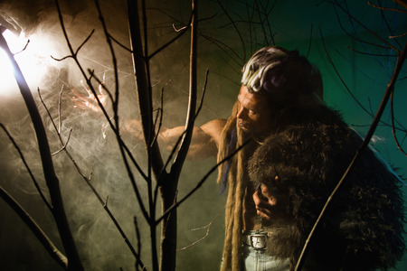 Muscular man with skin and dreadlocks looking at a bright light source. Werewolf in the woods photo