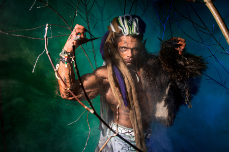 Muscular man with dreadlocks and skin through the trees. Werewolf in the woods. photo