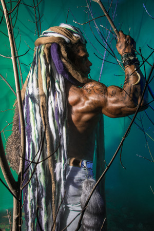 Muscular man in profile with dreadlocks in the forest. photo