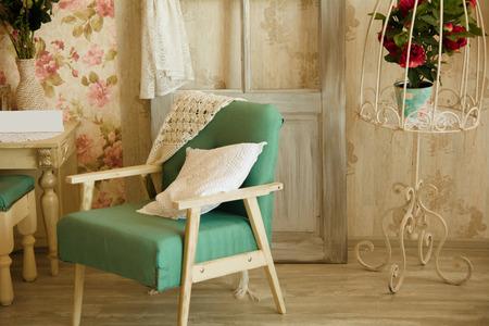 silla: Sitio interior con sillas, almohadas, puertas y flores. Habitación de estilo retro.